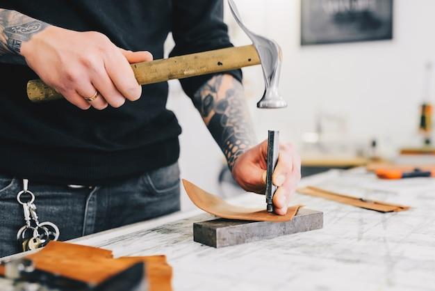 Feche acima de um artesão de couro que trabalha com couro usando o martelo.