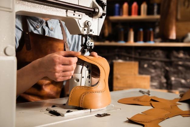 Feche acima de um artesão masculino que costura as peças de couro