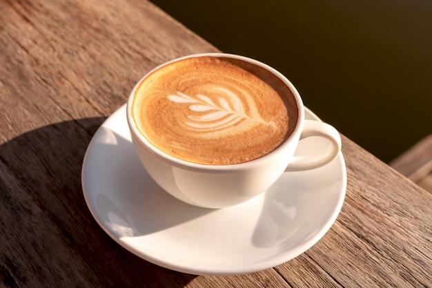 Feche acima de um café com leite em copo branco e espuma de leite acima para beber na mesa de madeira marrom