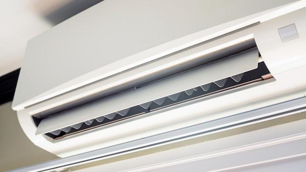 Feche acima de um condicionador de ar branco em um quarto.