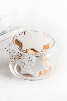 Feche acima de um frasco de vidro cheio de biscoitos caseiros de estrelas de natal.