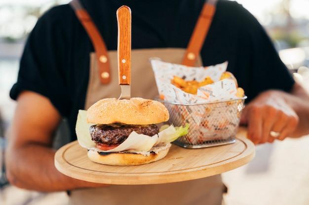Feche acima de um garçom que serve um delicioso hambúrguer, batatas fritas e molho servido em tábuas de madeira.