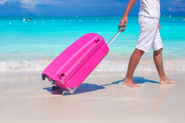 Feche acima de um homem puxa a bagagem na areia branca