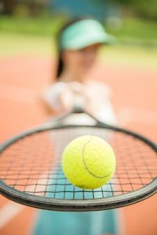 Feche acima de um jogador de ténis que bate a bola com raquete.