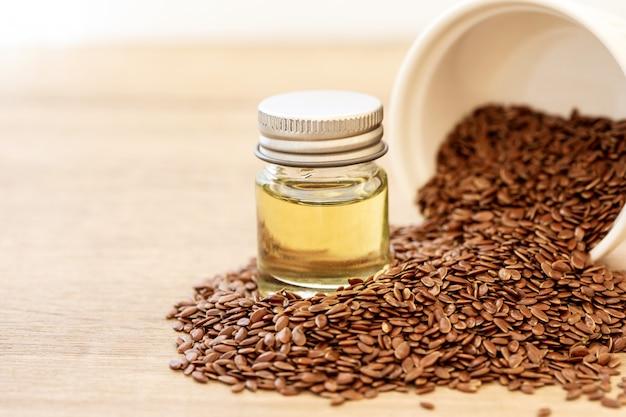 Feche acima de um óleo essencial e de sementes de linhaça na colher de madeira, alimento saudável do coração que superalimento e rico do ômega 3