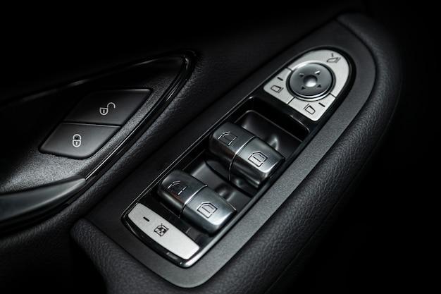 Feche acima de um painel de controle da porta em um carro moderno novo. apoio de braço com painel de controle da janela