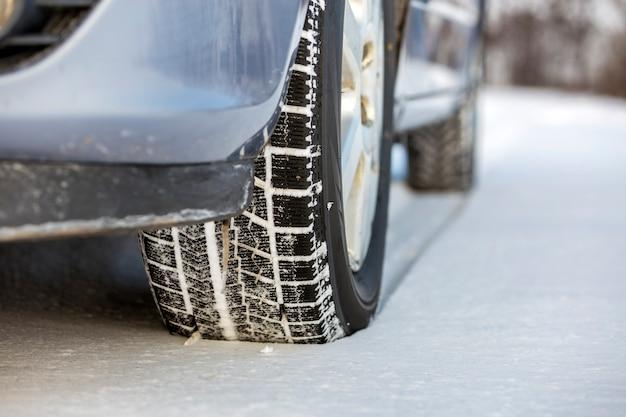 Feche acima de um pneu de carro estacionado na estrada nevado no dia de inverno. transporte e conceito de segurança.