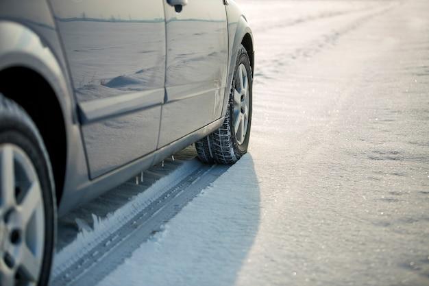 Feche acima de um pneu de carro estacionado na estrada nevado no dia de inverno. transporte e segurança.