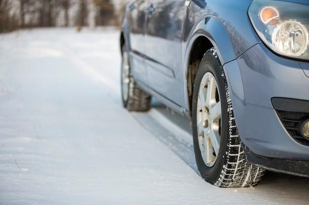Feche acima de um pneu de carro estacionado na estrada nevado no dia de inverno.