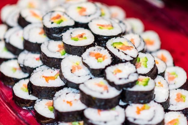 Feche acima de um prato cheio com rolos de sushi.