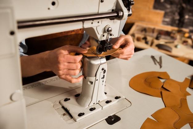 Feche acima de um sapateiro usando a máquina de costura