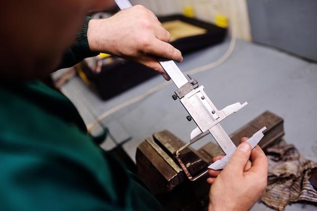 Feche acima de um trabalhador detém um paquímetro nas mãos e mede um detalhe
