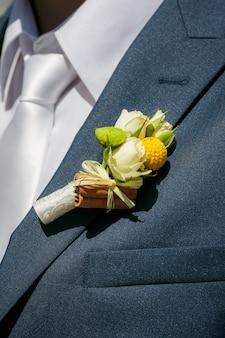 Feche acima de uma botoeira do noivo de rosas bege e canela