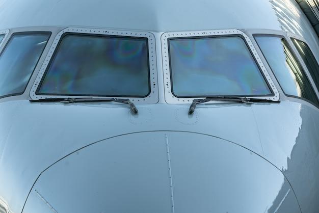 Feche acima de uma cabina do piloto do avião do jato vista dianteira da janela do avião com limpadores de para-brisa.