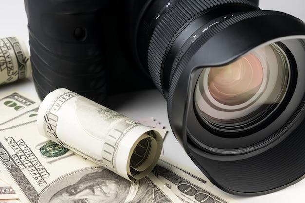 Feche acima de uma câmara digital preta em notas de banco com fundo branco.