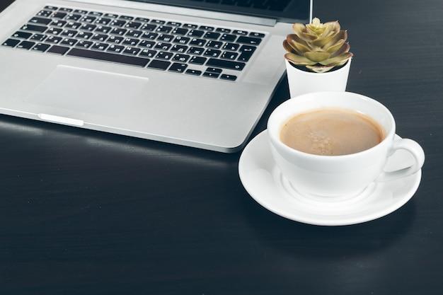 Feche acima de uma caneca de café no interior da mesa de escritório