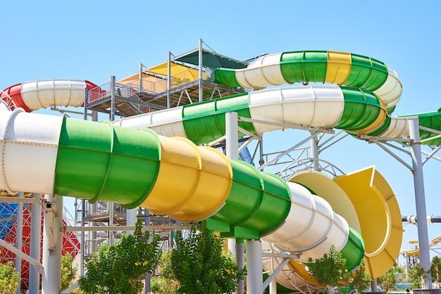 Feche acima de uma corrediça de água do tubo no parque aquático contra o céu azul