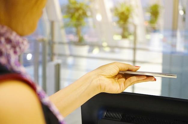 Feche acima de uma fêmea com os passaportes que mostram no contador de registro no aeroporto internacional.