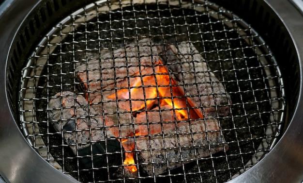 Feche acima de uma grade do carvão vegetal e de uma cesta do churrasco.