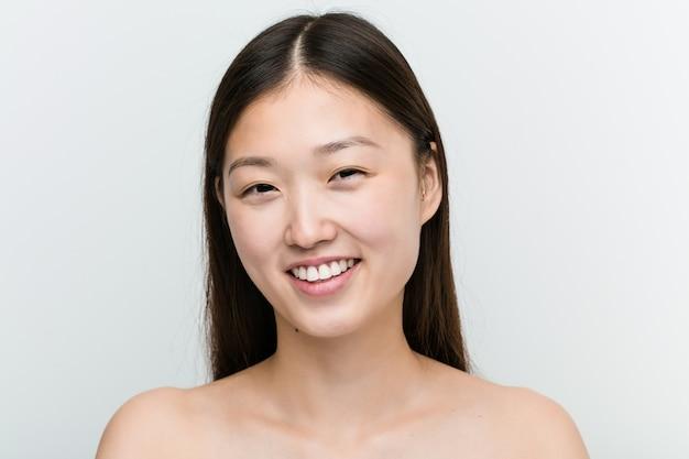 Feche acima de uma jovem mulher asiática bonita e natural