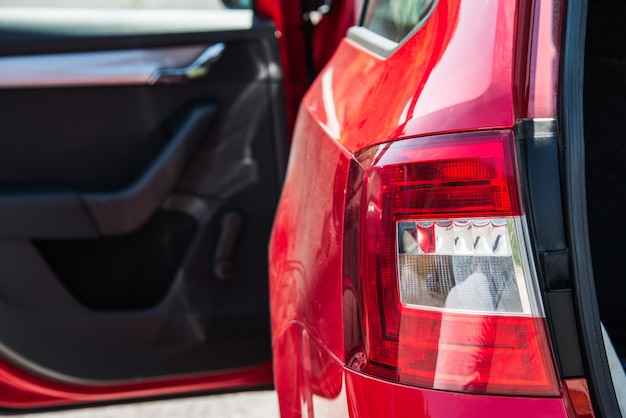 Feche acima de uma luz traseira do carro de um carro vermelho com a porta lateral aberta e o tronco.