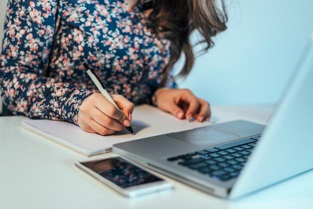 Feche acima de uma mão da mulher que escreve um contrato com um portátil ao lado.