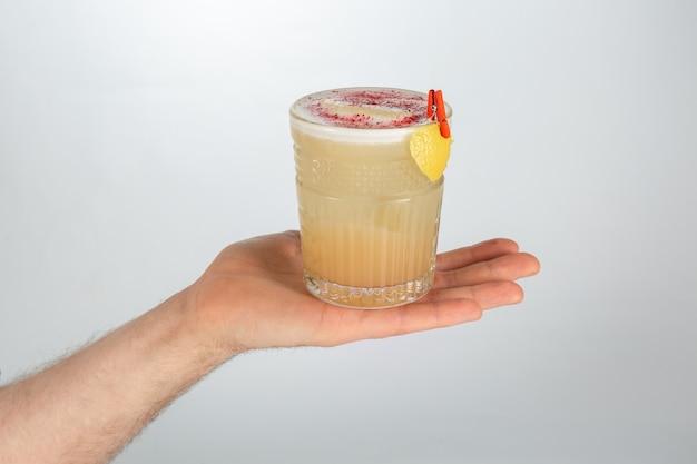 Feche acima de uma mão que guarda um copo do cocktail ácido do uísque no branco com espaço da cópia.