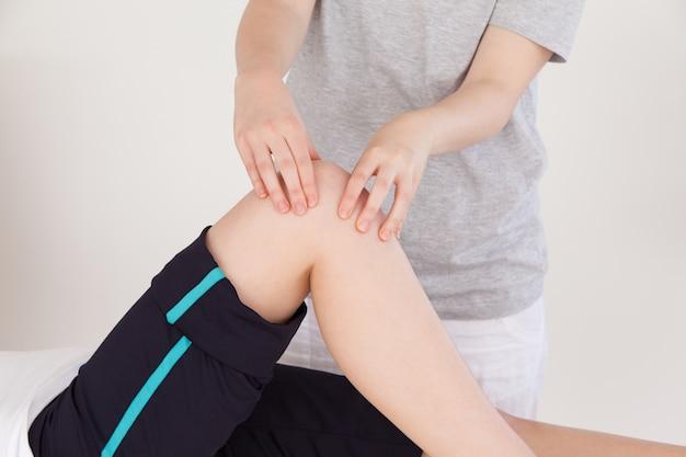 Feche acima de uma massagista aglomerando o joelho de uma mulher atlética
