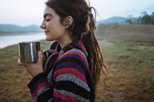 Feche acima de uma mulher de beleza beber uma xícara de café depois de acordar