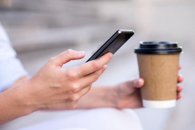 Feche acima de uma mulher de negócios usando o telefone móvel e segurando o copo de papel. close-up detalhe de uma mulher de negócios segurando copo de papel e usando um smartphone