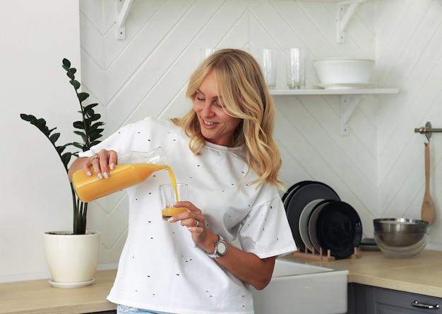 Feche acima de uma mulher de sorriso com sumo de laranja e vidro na cozinha.