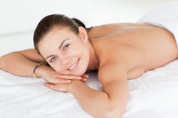 Feche acima de uma mulher deitada em uma mesa de massagem olhando a câmera