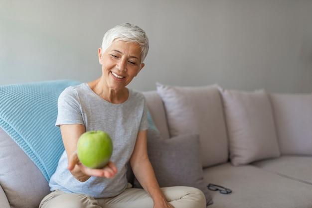 Feche acima de uma mulher idosa alegre que come uma maçã ao sorrir em casa.