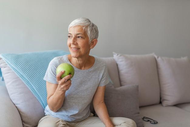 Feche acima de uma mulher idosa alegre que come uma maçã ao sorrir na sala de visitas.