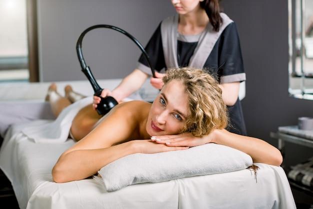 Feche acima de uma mulher loura consideravelmente sorridente, recebendo tratamento de cavitação por ultrassom pelo cosmetologista. mulher encantadora, desfrutando de terapia de contorno corporal na clínica de spa