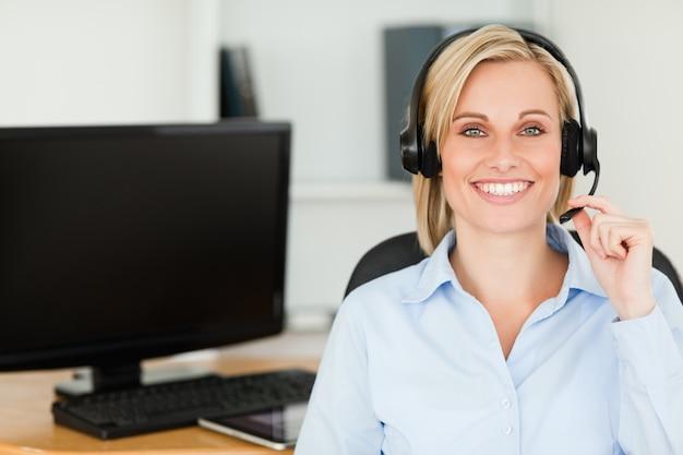 Feche acima de uma mulher sorridente loira vestindo fone de ouvido olhando para a câmera