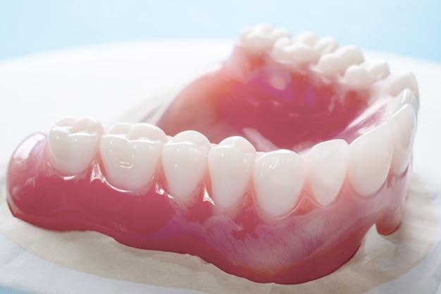 Feche acima, dentadura completa ou dentadura completa no fundo azul.