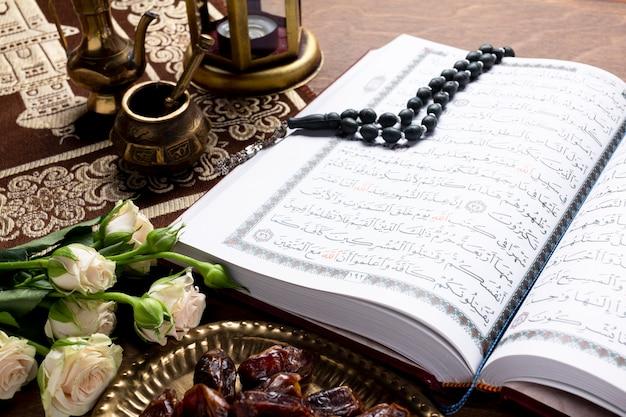 Feche acima do alcorão aberto e itens islâmicos