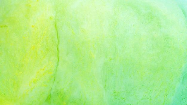 Feche acima do algodão doce verde para um fundo.