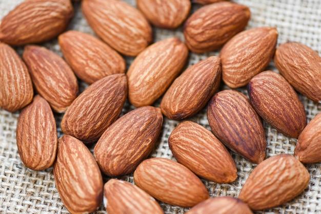 Feche acima do alimento natural da proteína das amêndoas e no lanche - amêndoas no fundo do saco