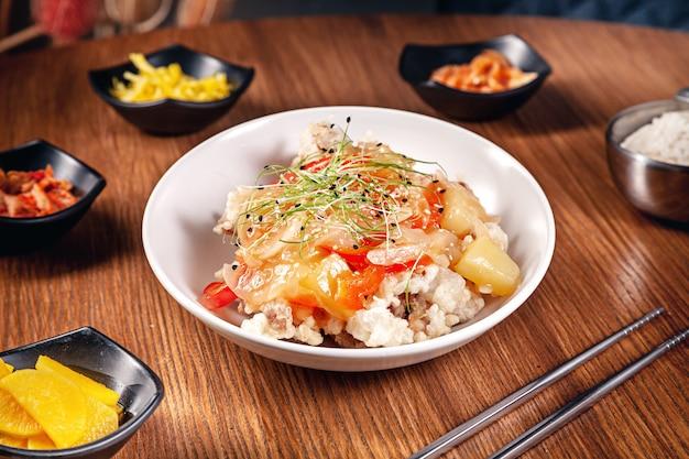 Feche acima do alimento tradicional coreano com kimchi no fundo de madeira. arroz coreano com cebola, molho vermelho e gergelim, carne de frango. cozinha asiática tradicional. almoço. comida saudável