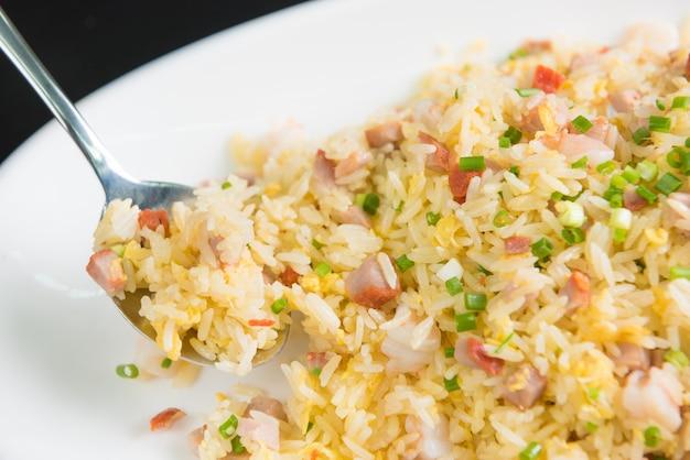 Feche acima do arroz frito na colher no prato branco no fundo preto