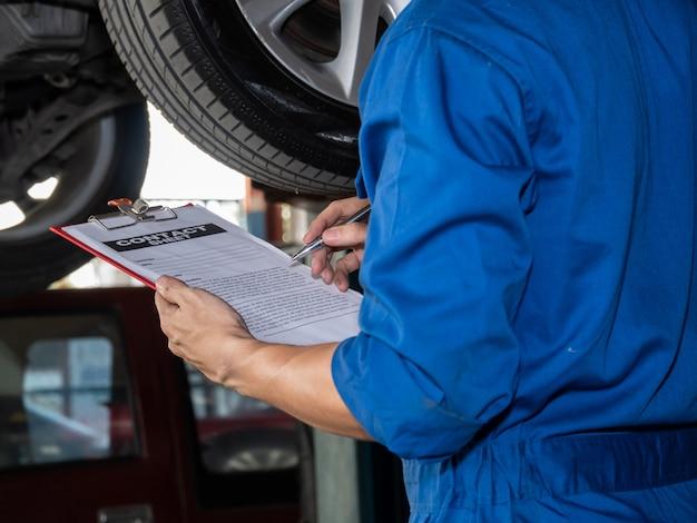 Feche acima do auto mecânico no uniforme que guarda o original do contrato.