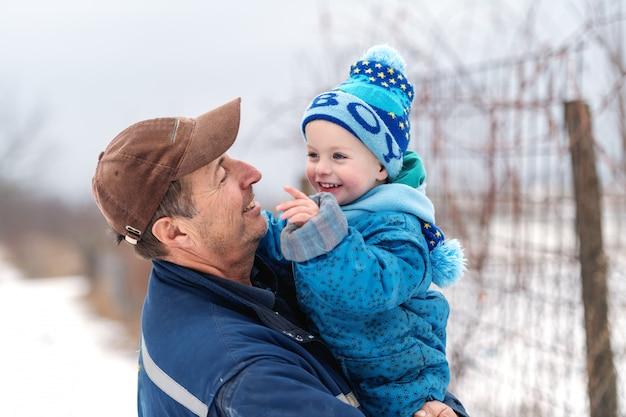 Feche acima do avô de sorriso que guarda seu neto no tempo frio. ambos vestidos com roupas quentes de inverno.