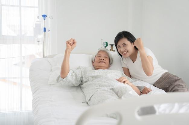 Feche acima do avô paciente e mulheres de mãos dadas na cama de hospital