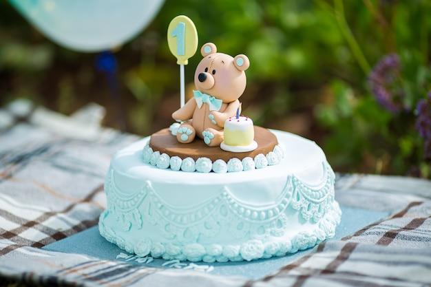 Feche acima do bolo surpreendente para o primeiro aniversário do menino. cores azuis e brancas com filhote de urso de mástique de açúcar