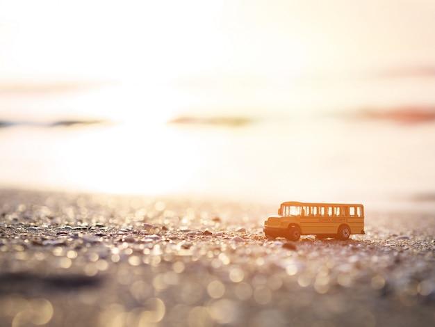 Feche acima do brinquedo amarelo do ônibus escolar na areia na praia do por do sol.