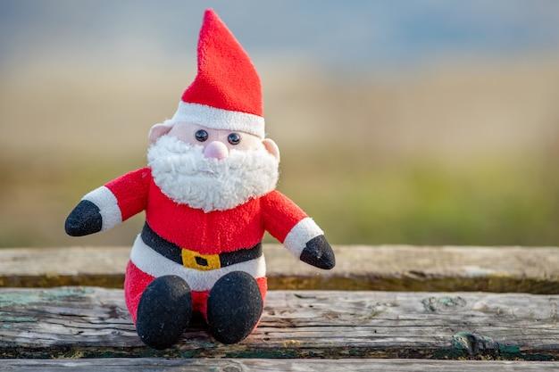 Feche acima do brinquedo pequeno de papai noel no banco de madeira ao ar livre.