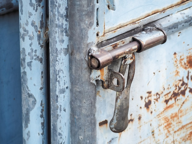 Feche acima do buraco da fechadura enferrujado na porta de aço azul