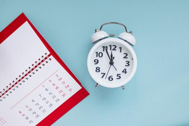Feche acima do calendário e despertador no fundo azul, planejando a reunião de negócios ou o conceito de planejamento de viagens